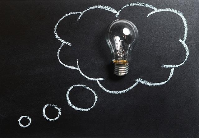 電球が黒板に書かれた考えるマークの中に乗っている。