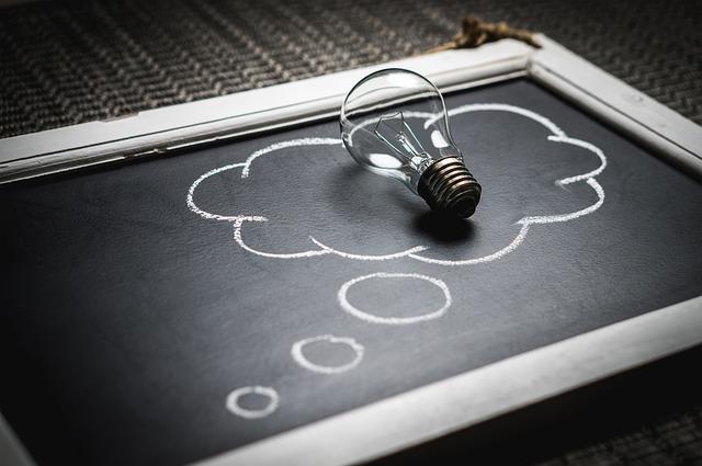 電球が黒板に書かれた考えるマークの中に乗っているのを横から写してある。