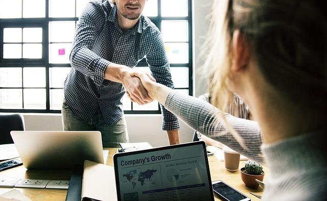 パソコンの上で握手をしている写真です。