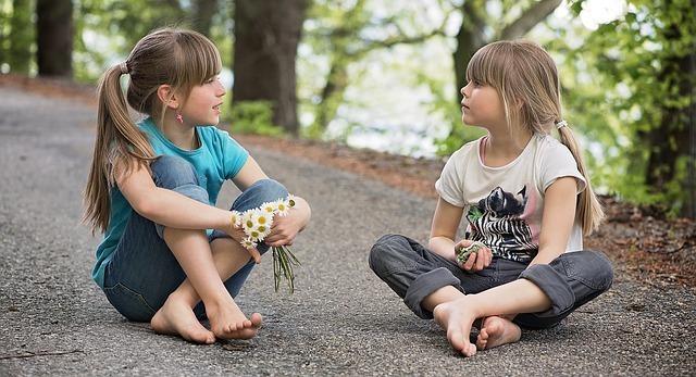 女の子が2人道に座り込んで話している写真です。