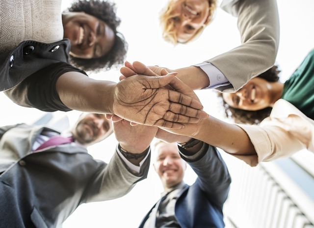 5人の外国人が手を重ねている写真です