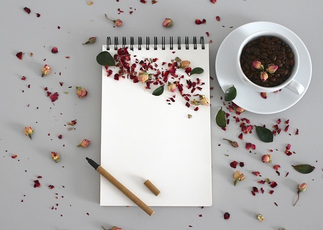 ノートとボールペンとコーヒーとバラの花