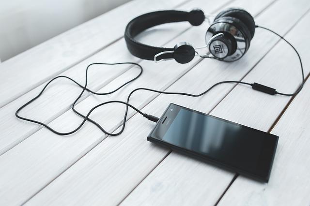 シルバーのヘッドフォントと黒のスマートフォンの写真です。