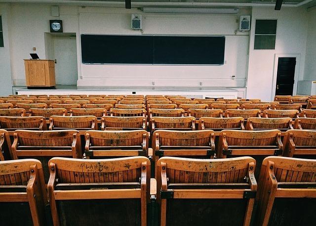 黒板と教卓と椅子がある教室の写真です。