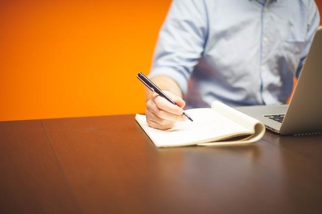 男の人がノートに書いている写真です。