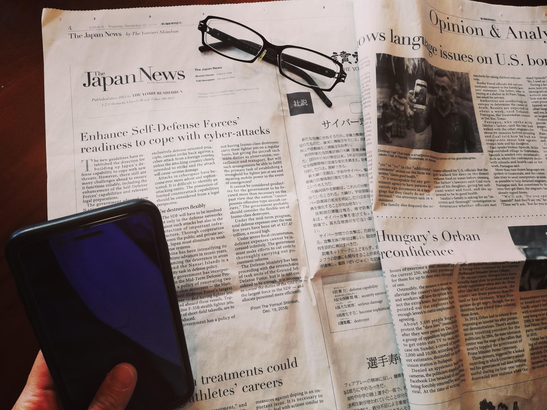 英字新聞とメガネとスマートフォンの写真です。