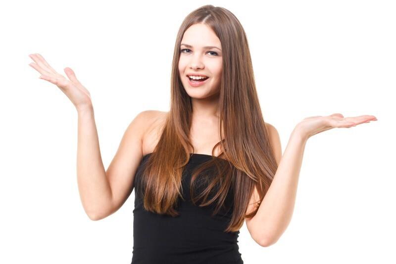 両手を上げて分からないポーズを取る女性
