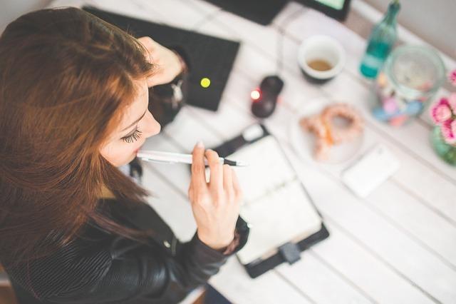外国人女性がペンを持って考えている写真