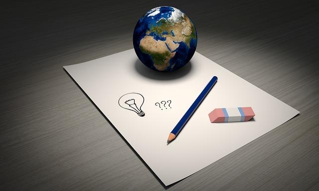 紙の上にアイデアの絵が描いてあり、地球儀と鉛筆と消しゴムが置いてある写真