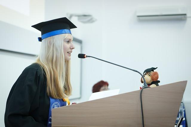 スピーチする金髪女性の写真です。
