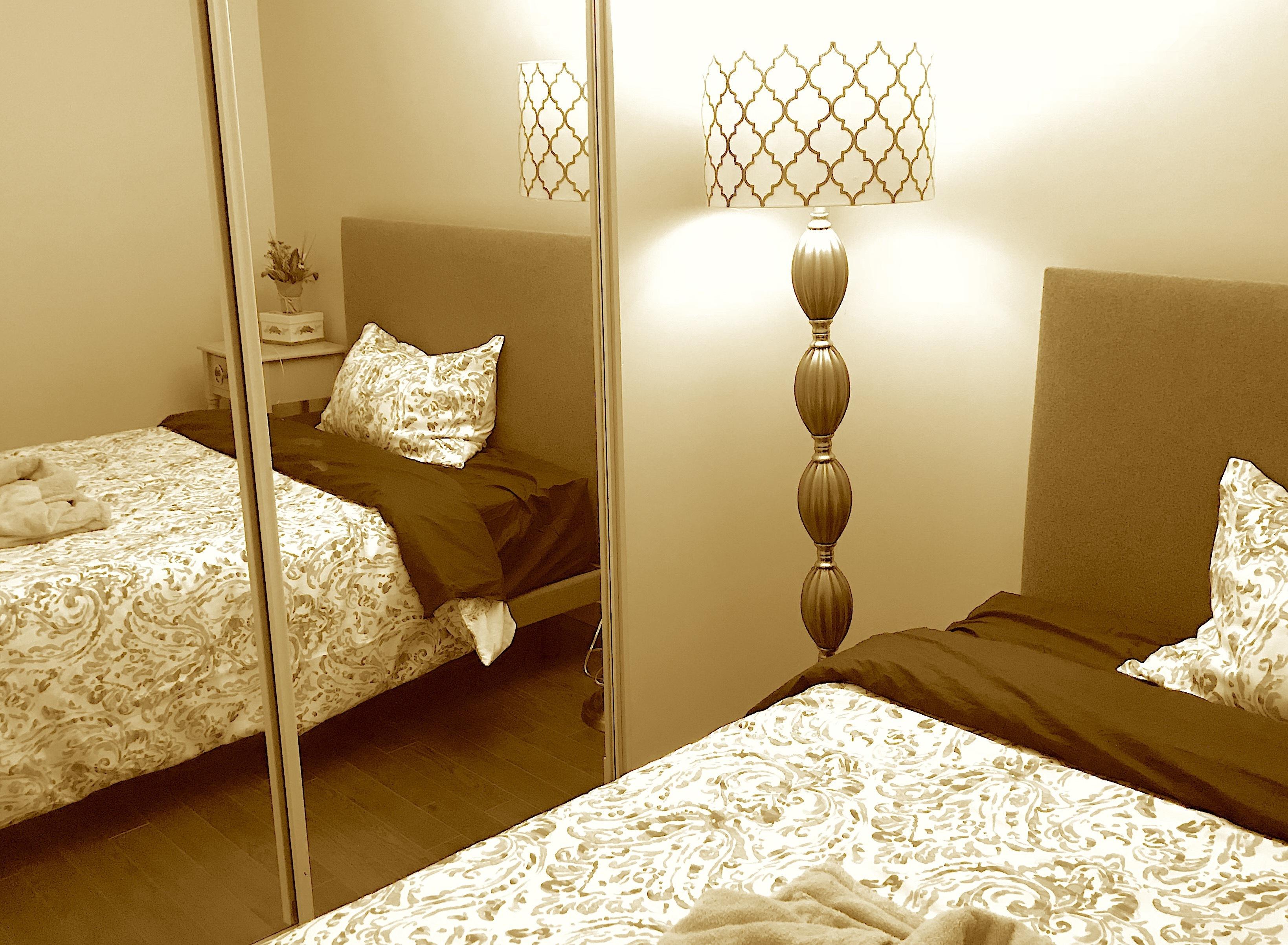 大きい窓と明るいライトのあるベッドルーム写真(セピア)。