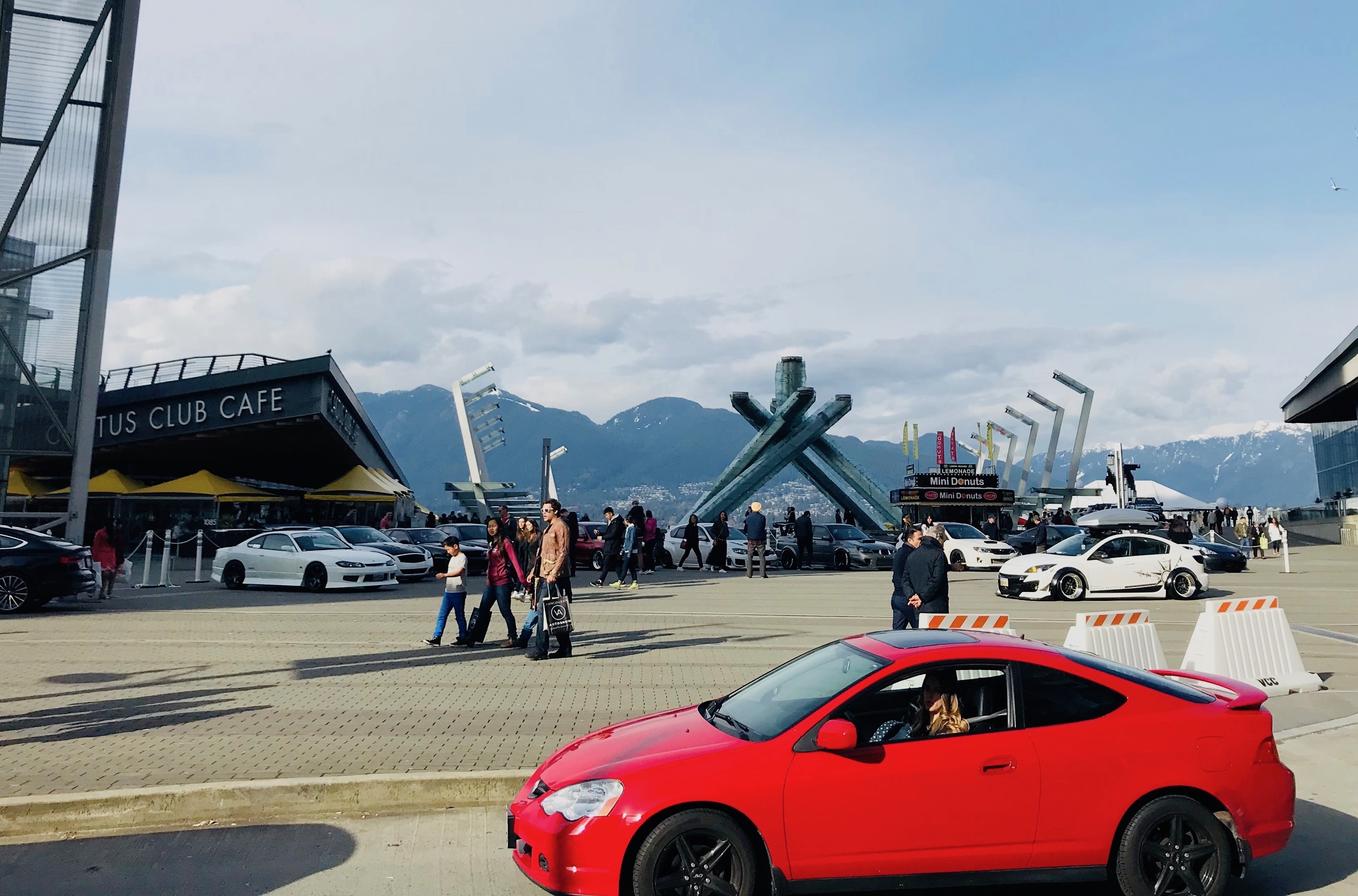 真っ赤なスポーツカーとカナダプレイス(バンクーバー)の聖火台。