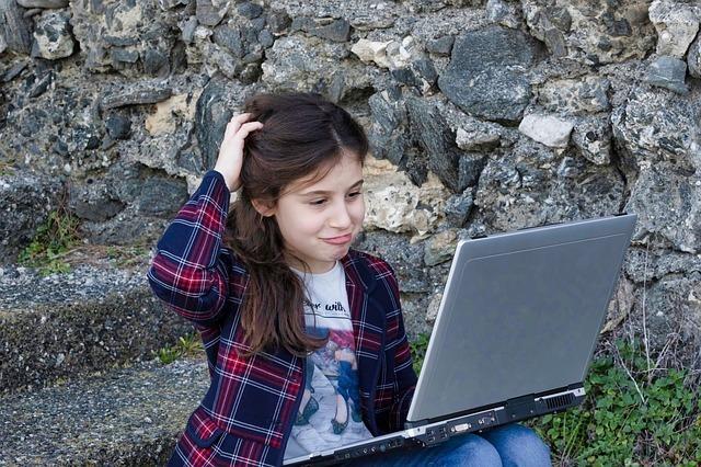 ノートパソコンを見ながら少女が頭を抱えている写真です。