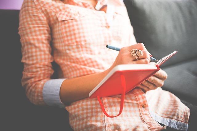 オレンジ色のチェックの服を着た女性がノートを取っている写真です。