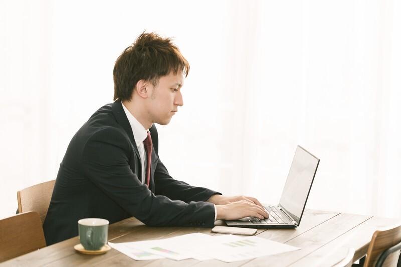 男性がノートパソコンに何か打ち込んでいる写真です。