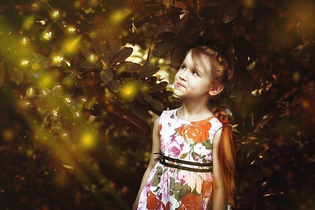 ドレスを着た女の子が光の方を見ている