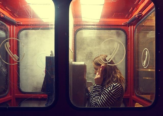 公衆電話で話す外人女性
