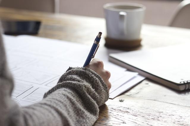 机で女性がなにかを書いている