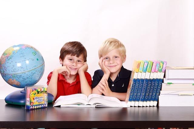 子供二人が本を開いて微笑んでいる