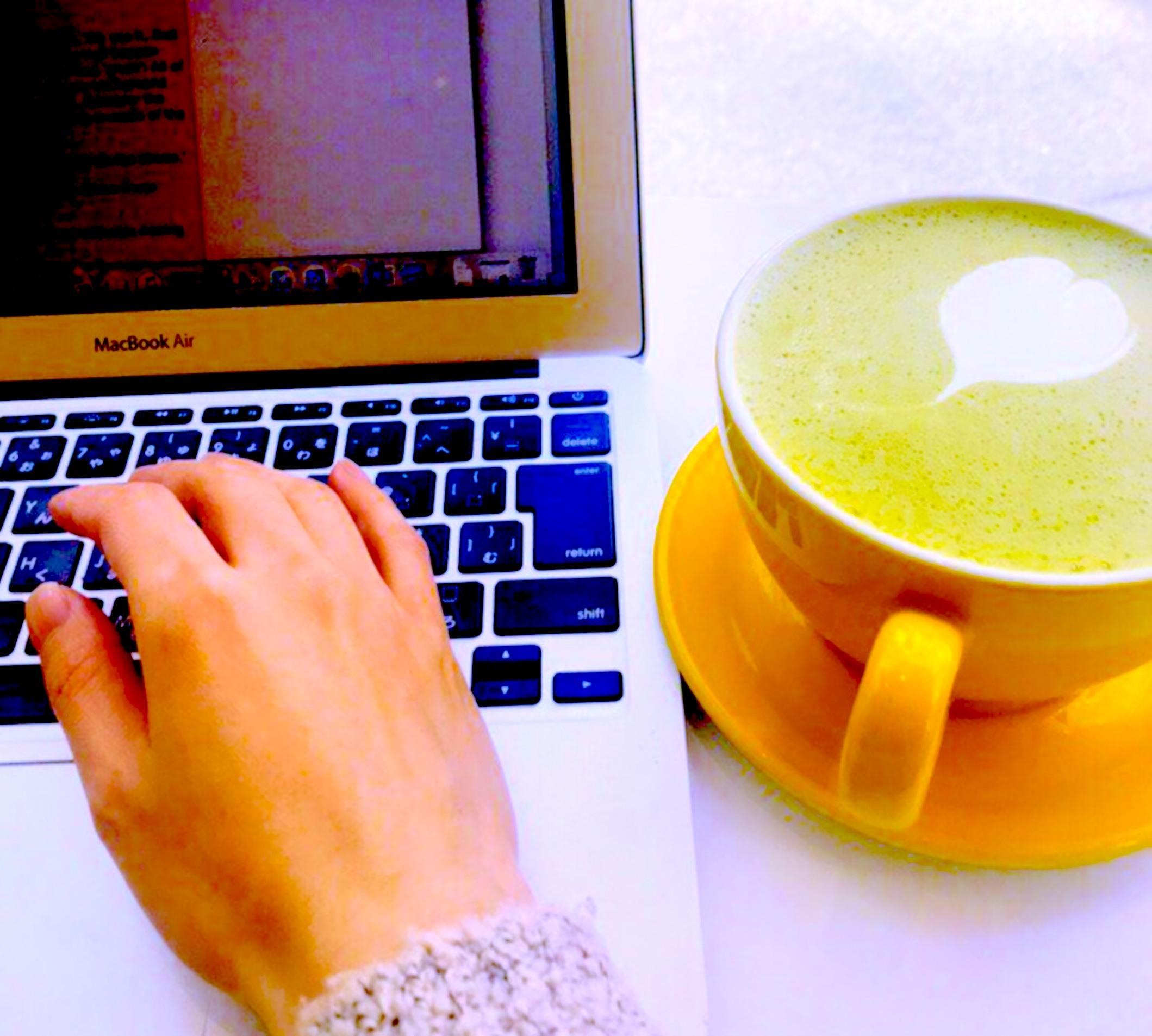 抹茶ラテとパソコンで作業をする手。ラテアートのハート。