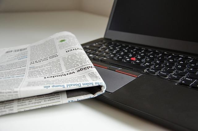 ノートパソコンと新聞の写真