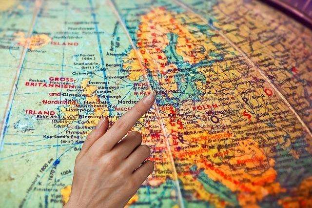 人が地球儀を見ながら外国旅行を考えている