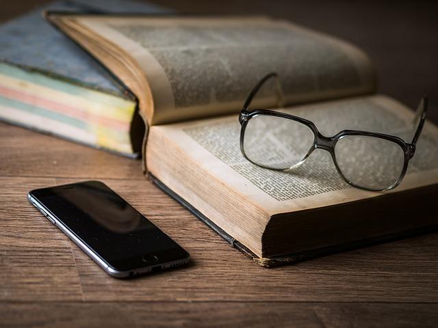 テーブルの上に辞書とスマートフォンが置かれている写真です。