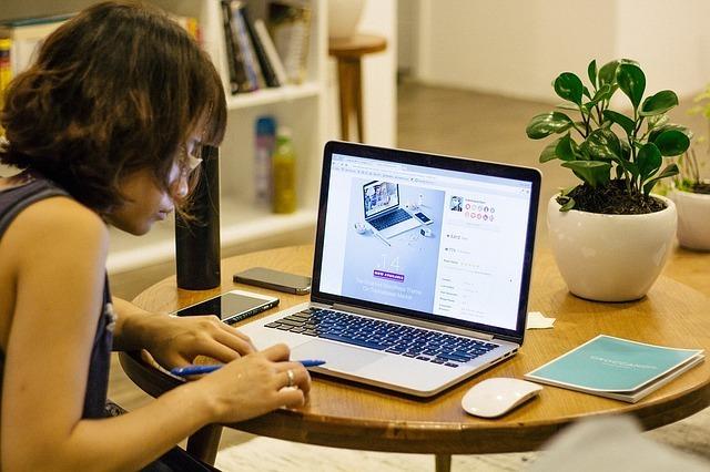 女性がパソコンを開きながらメモをしている写真です。