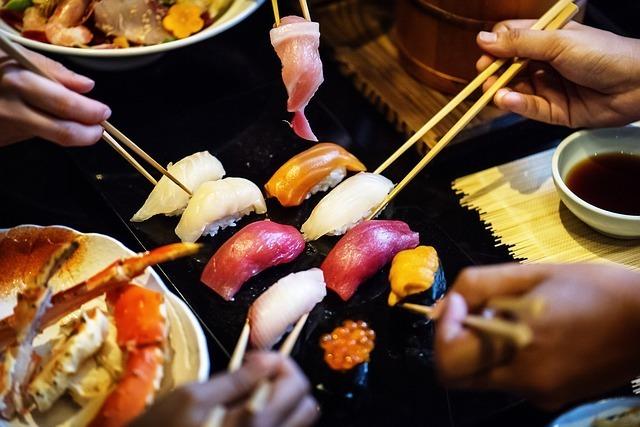 5人が箸でお寿司を食べている