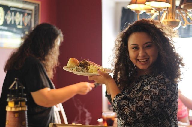 ホームパーティーで料理を盛ったお皿を持つ女性