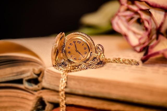 古い本の上に懐中時計が置いてある写真