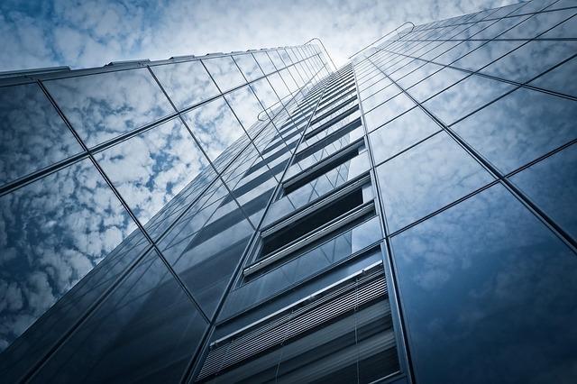 ビルの窓ガラスに青空と雲が写っている写真