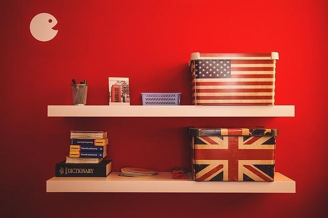 赤い壁の部屋にイギリスとアメリカの国旗の柄の箱が飾ってある写真