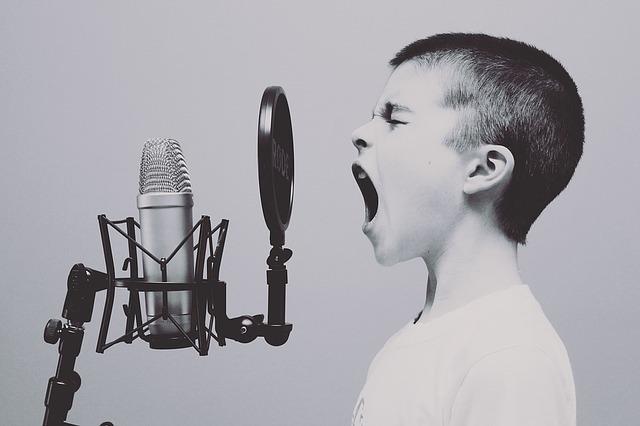 男の子がマイクの前で口を大きく開けて歌っている写真