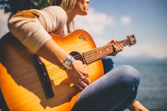 海のそばで女性がギターを抱えて弾き語りしている写真
