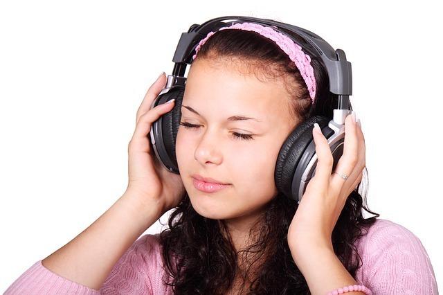 ピンクの服を着た女性がヘッドフォンで音楽を聴いている写真