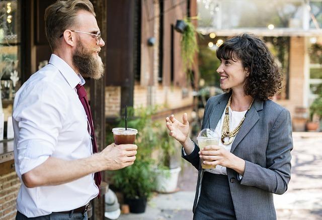 コーヒーを片手に語り合う男女の写真