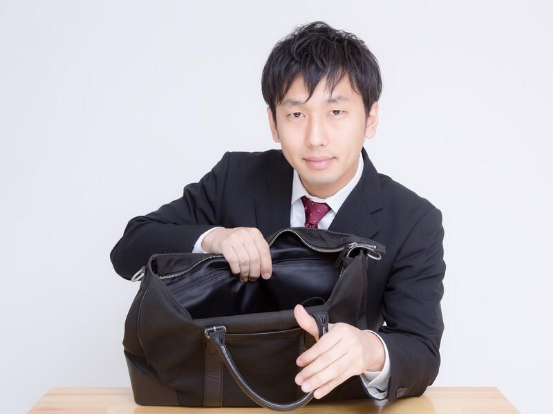 スーツ姿の男の人が鞄の中を見せようとしている写真
