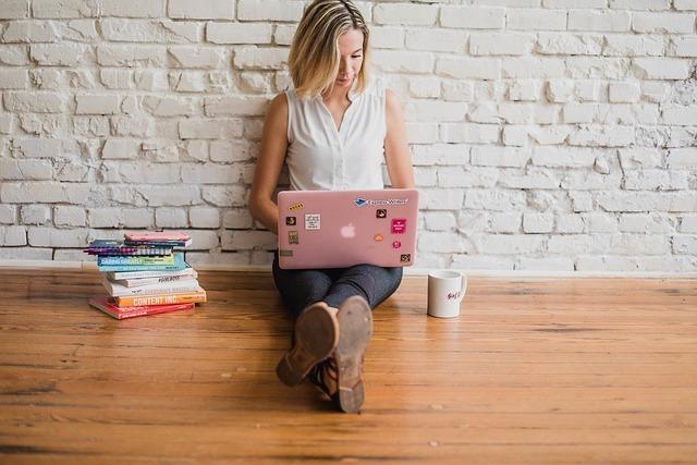 女の人が床に座ってパソコンを使っている写真