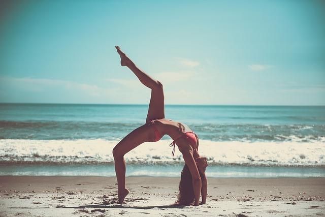 女性が浜辺でエクササイズをしています。