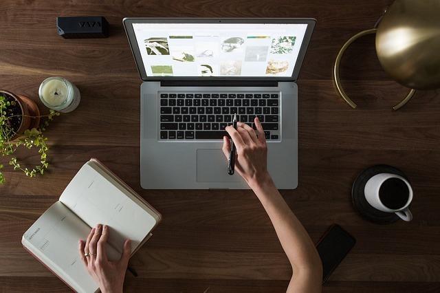 コンピューターと手帳で仕事