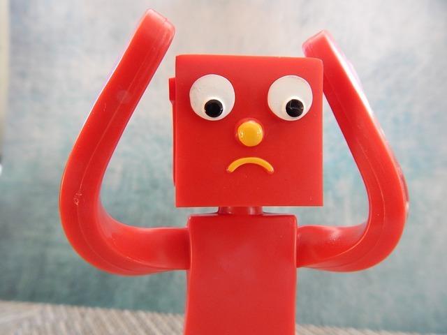 手を上げて困っている赤いプラスチック製のおもちゃ