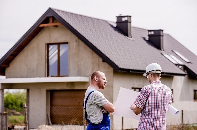 家屋の建築現場で話し合うふたりの男性