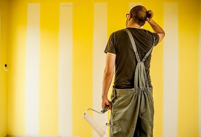 黄色い壁にローラーで白いペンキを塗る男性