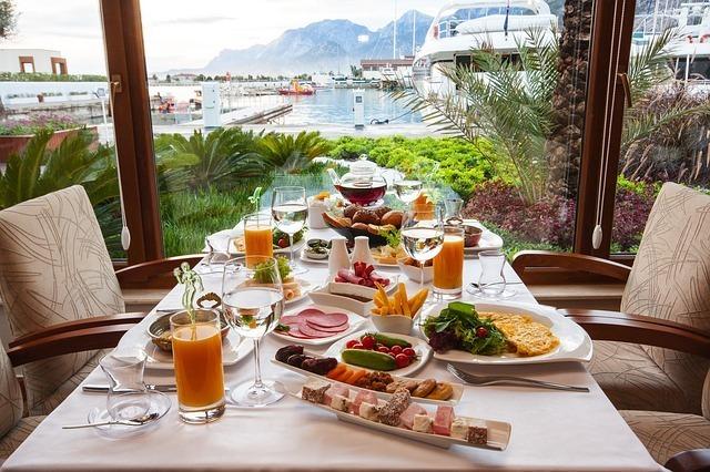 海が見える窓際のテーブル席に料理が配膳されている写真