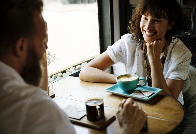 男性と女性がカフェで談笑している画像