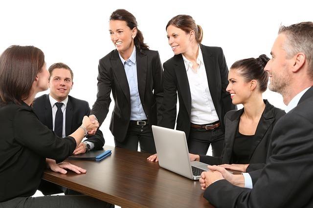 女性2人が握手するのを見る男女