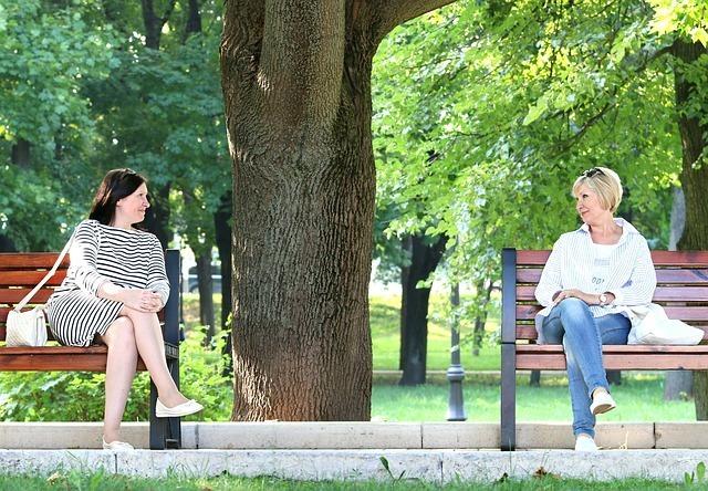 外国人女性がベンチに座って会話している写真