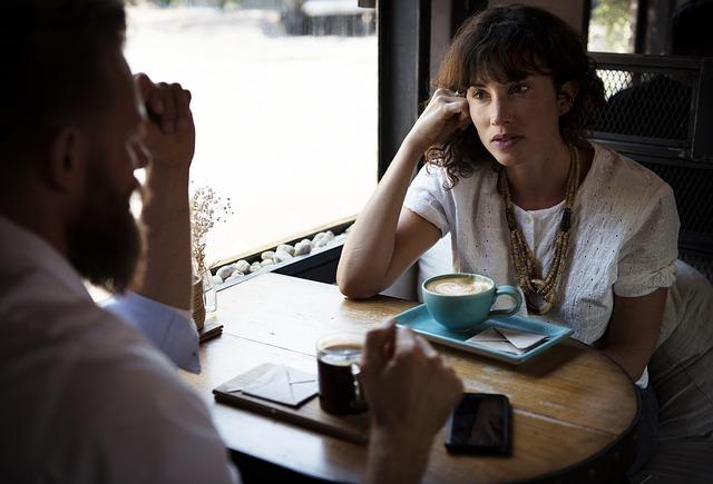 カフェでコーヒーを飲みながら話す一組の男女