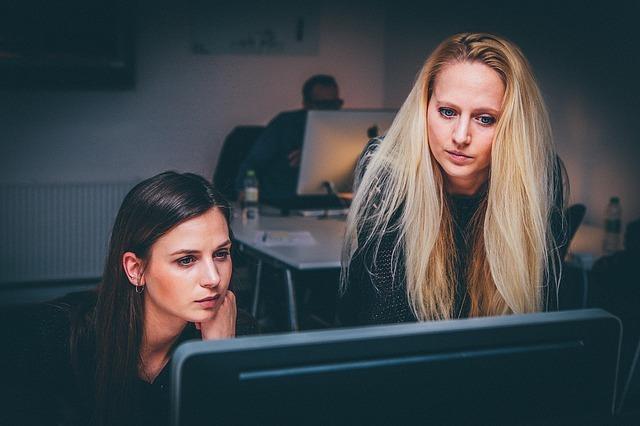 デスクトップの前で話す二人の髪の長い女性